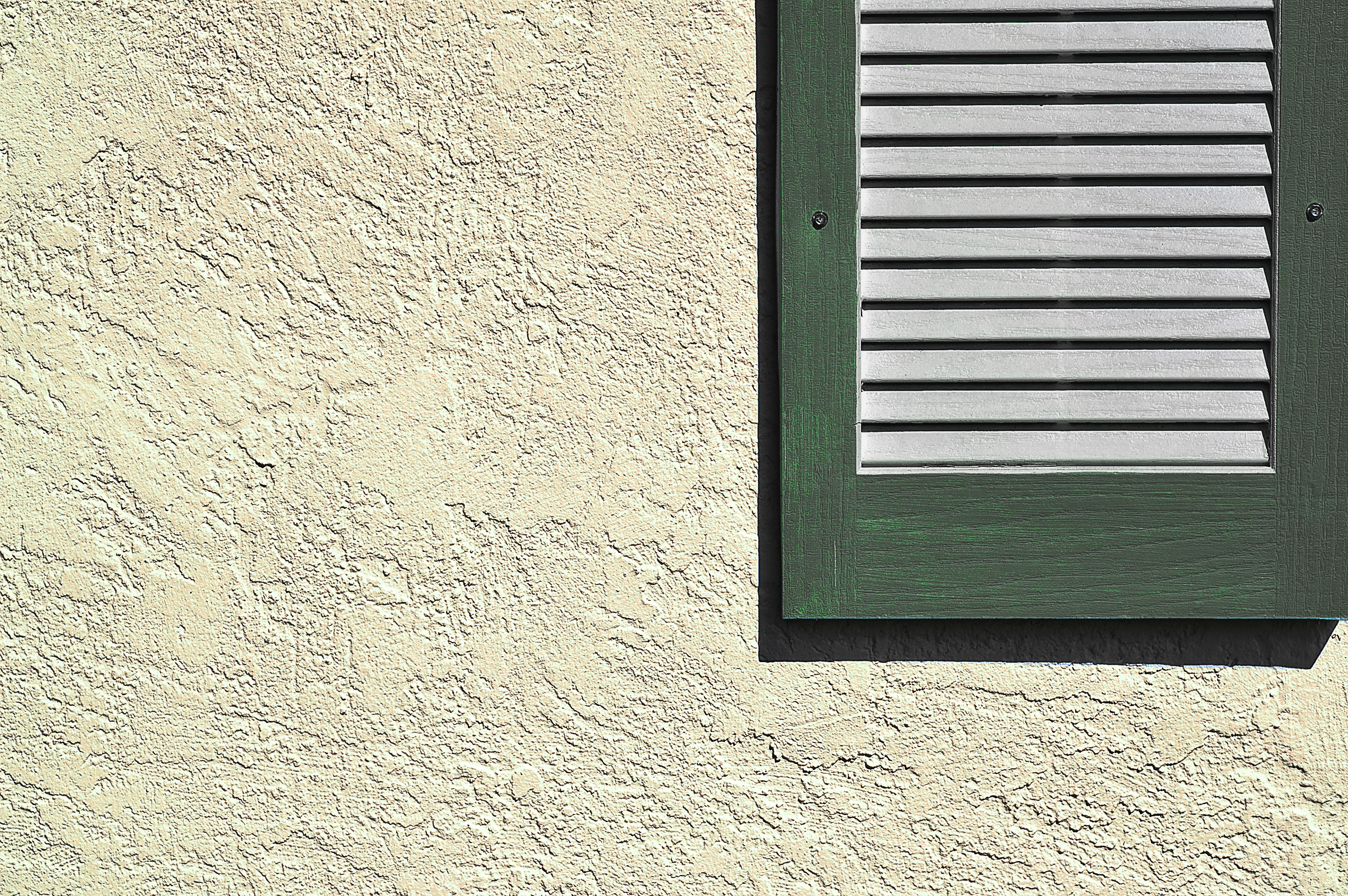 Green shutter on exterior stucco wall