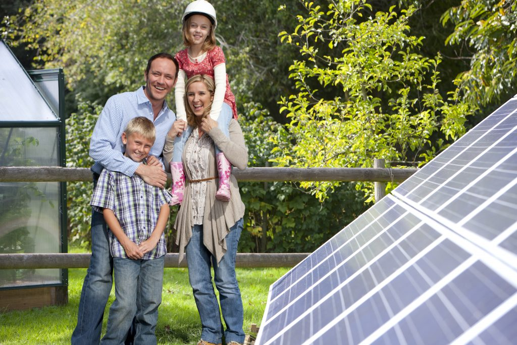 family in front of solar panels in the backyard