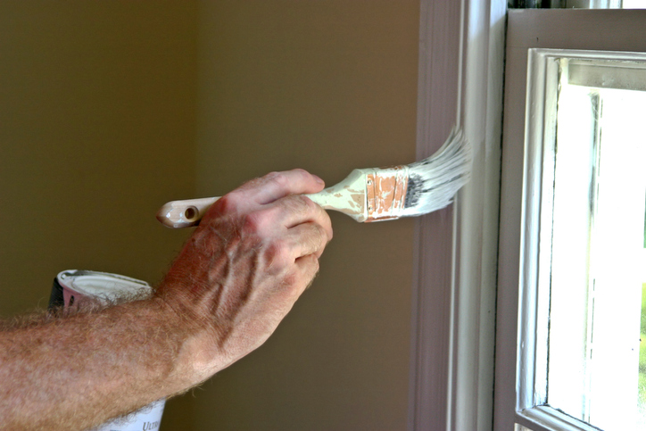 Close up of a man's arm and hand holding a paint brush and painting white latex paint on an interior window frame