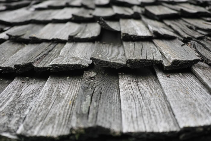 Roof wood shingles rot and warp after storm damage.