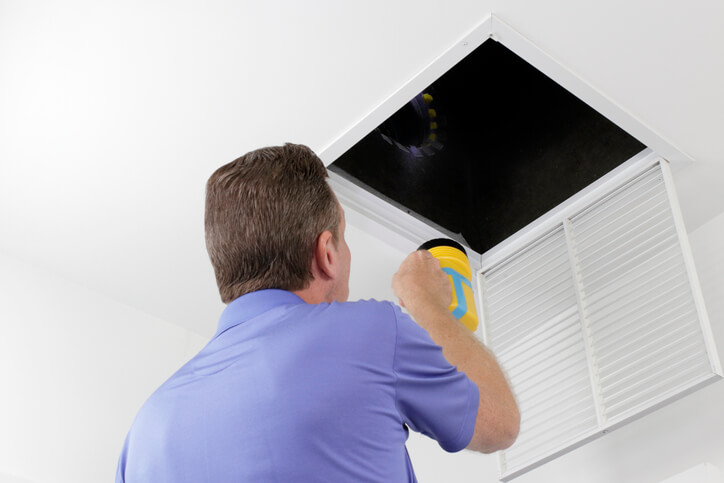 Man inspecting an air duct for replacement